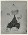 A Caucasian baby dressed in a dark colored jumpsuit with a white overcoat by Lonnie W. Fleming Sr.