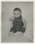 A Caucasian baby dressed in dark colored overalls and wearing a striped shirt underneath by Lonnie W. Fleming Sr.
