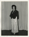 A Caucasian lady standing wearing a white formal gown and a dark colored fur coat by Lonnie W. Fleming Sr.