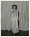 A Caucasian lady standing wearing a white formal gown by Lonnie W. Fleming Sr.