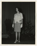 A Caucasian lady wearing a light dress suit and a dark skirt by Lonnie W. Fleming Sr.