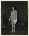 A Caucasian lady wearing a floral dress, white gloves, and light colored high heels by Lonnie W. Fleming Sr.