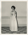 A Caucasian lady wearing a white formal dress with spaghetti straps by Lonnie W. Fleming Sr.