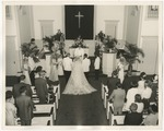 A bride, groom, and her father standing in a church facing the pastor by Lonnie W. Fleming Sr.