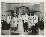 A bride and groom with their families at their sides by Lonnie W. Fleming Sr.