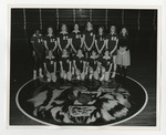 12 female athletes and their coach taking a group picture in the gymnasium by Lonnie W. Fleming Sr.