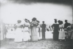 Women in formal attire looking at the strand and swimmers. by Horry County Historical Society